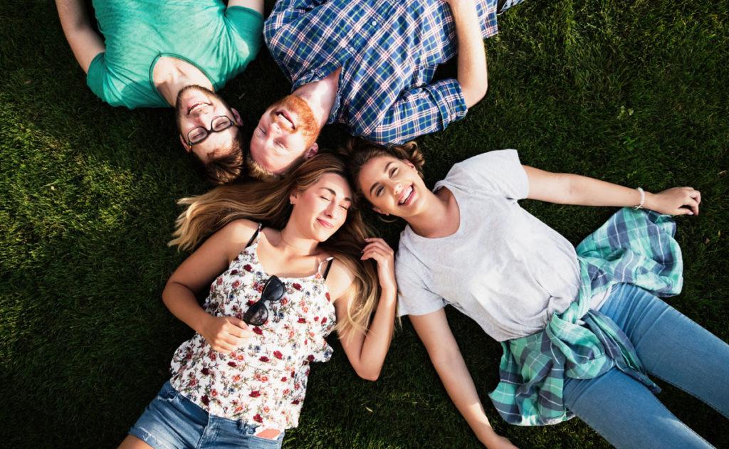 vier Freunde liegen auf einer Wiese